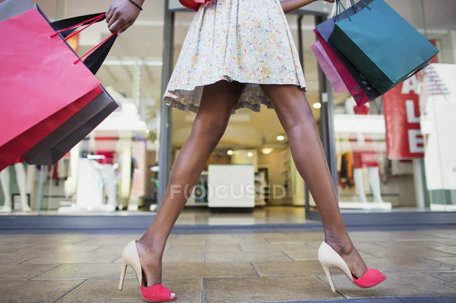 Woman carrying shopping bags in shopping mall — Stock Photo