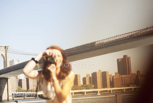 Mujer tomando fotos por puente urbano - foto de stock