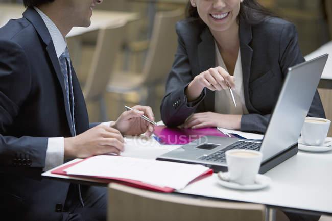 Sorrindo, empresário e mulher de negócios usando o laptop no café — Fotografia de Stock