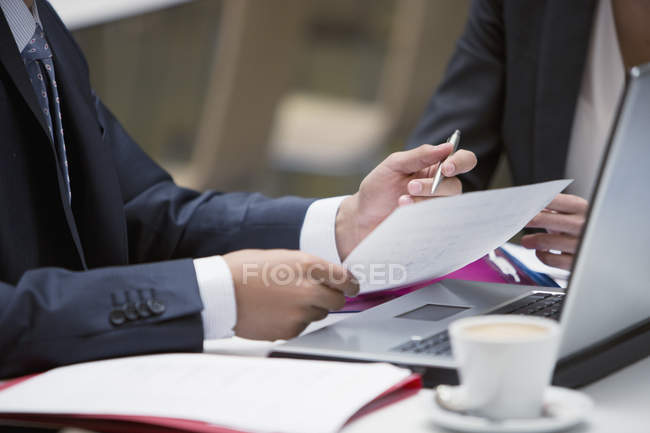 Close up of business people reviewing paperwork at cafe — Stock Photo