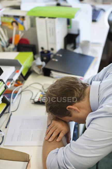 Empresário descansando cabeça na mesa no escritório moderno — Fotografia de Stock