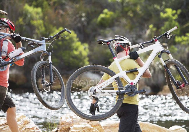 Caucasian adult men carrying mountain bikes in river — Stock Photo