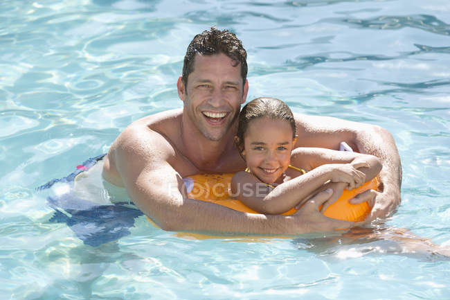 Father and daughter relaxing in swimming pool — Stock Photo