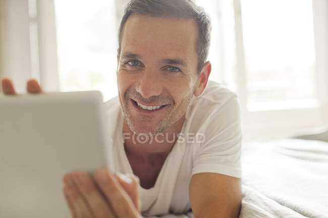 Portrait of smiling man using digital tablet in bed — Stock Photo