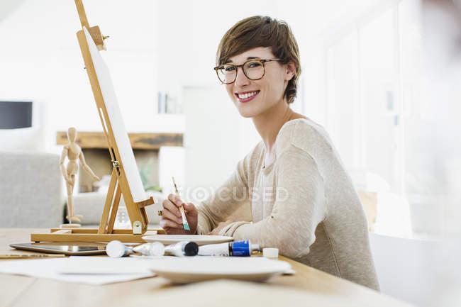 Retrato de mujer sonriente pintando al caballete sobre la mesa - foto de stock