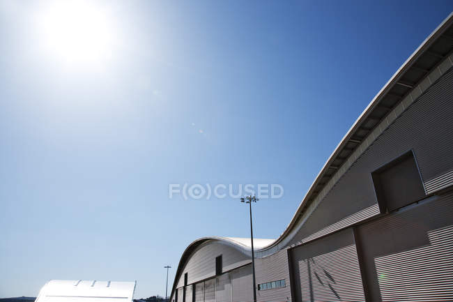 Curved roof of warehouse and blue sky — Stock Photo