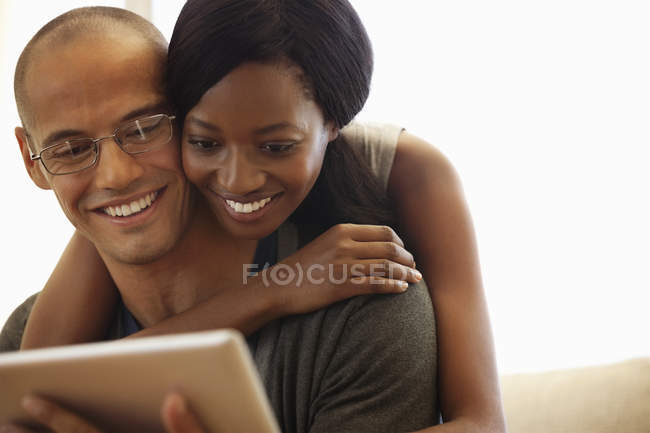 Young attractive Couple using tablet computer on sofa — Stock Photo
