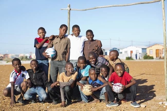 Африканские мальчики держат футбольные мячи в грязи — стоковое фото