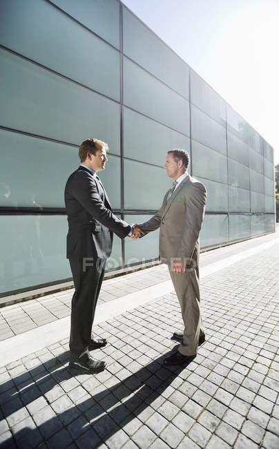 Бізнесмени рукостискань міста, на вулиці — стокове фото
