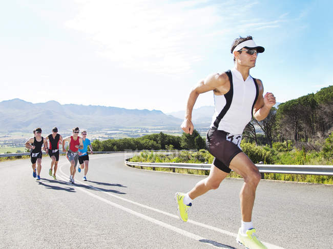 Runners in race on rural road — Stock Photo