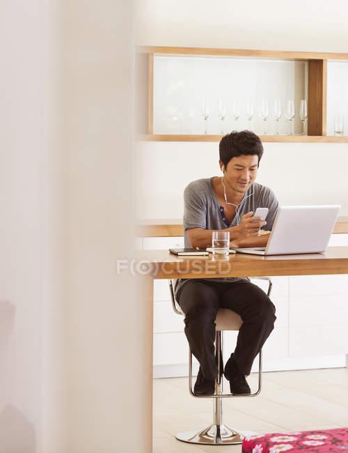 Mann mit Handy und Laptop am Tisch — Stockfoto