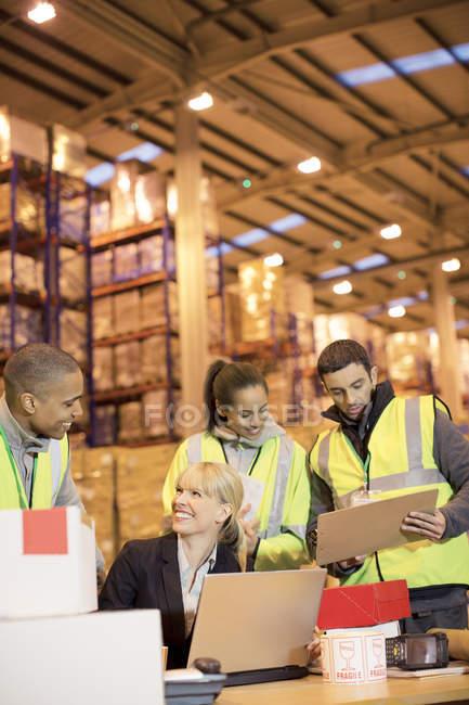 Empresária e trabalhadores conversando em armazém — Fotografia de Stock