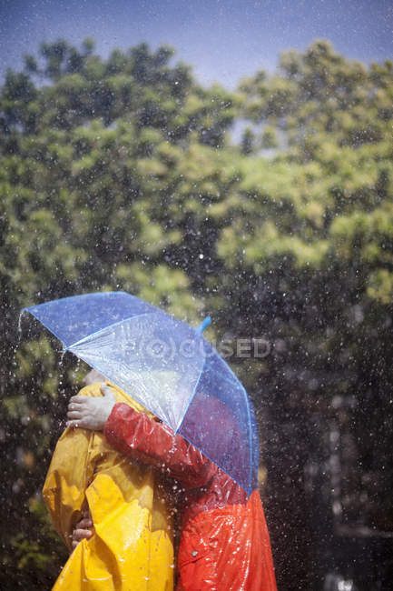 Pareja abrazándose bajo paraguas bajo la lluvia — Stock Photo
