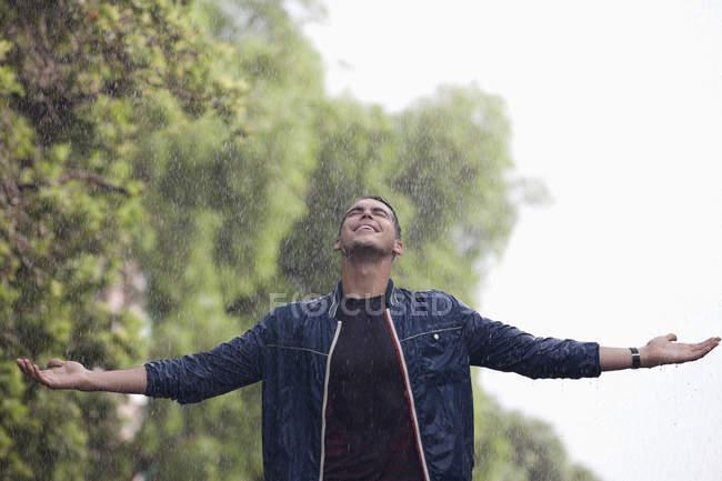 Человек с распростертыми руками под дождем — стоковое фото
