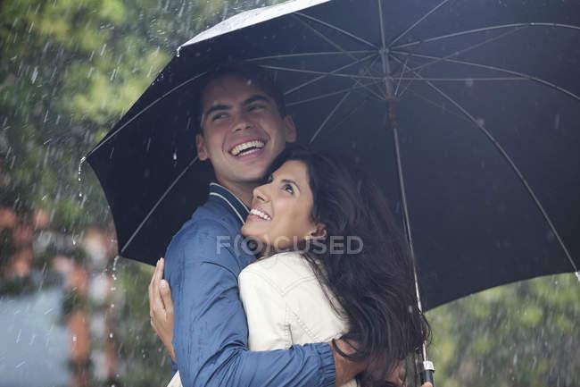 Счастливая пара обнимается под зонтиком под дождем — стоковое фото