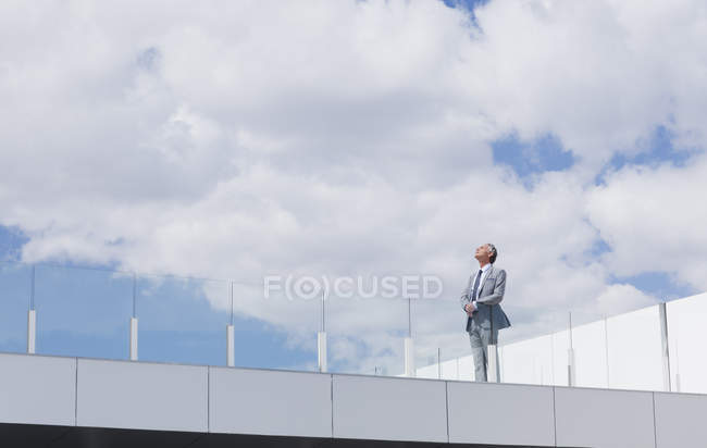 Pensive businessman looking up at sky on rooftop balcony — Stock Photo
