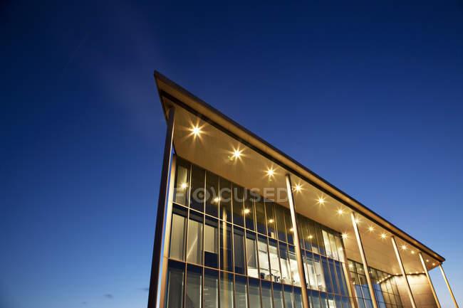 Modern building illuminated at dusk — Stock Photo