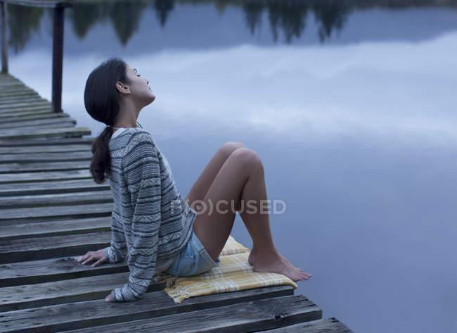 Serene woman sitting on dock over lake — Stock Photo