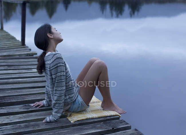 Serene woman sitting on dock over lake — Stock Photo