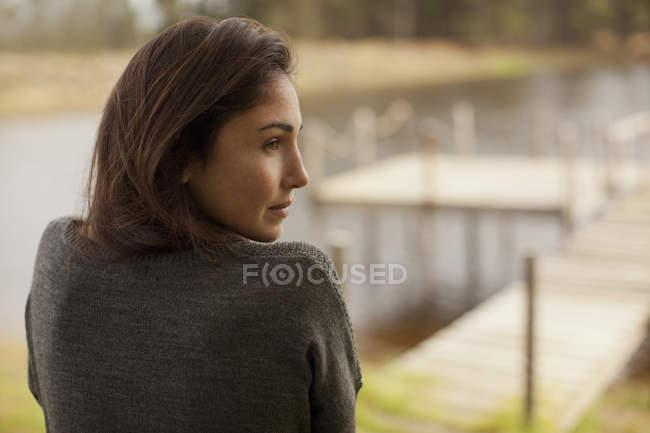 Pensive woman at lakeside — Stock Photo