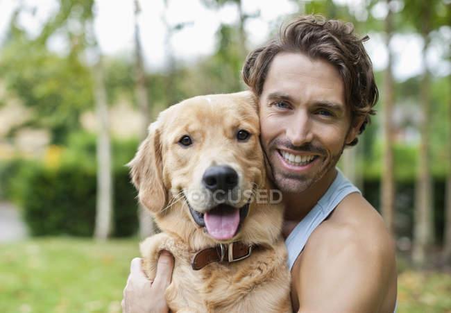 Homme caresser l'extérieur chien souriant — Photo de stock