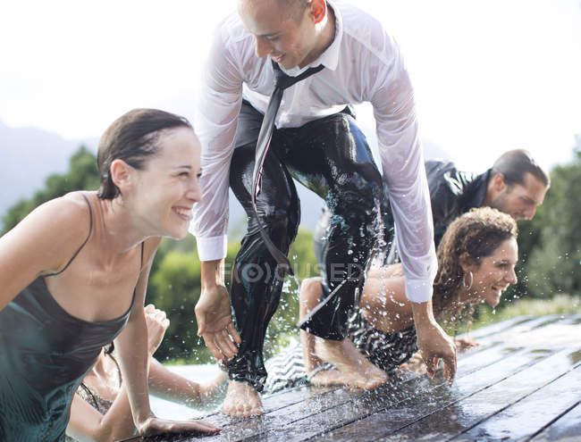 Fully dressed friends climbing out of swimming pool — Stock Photo
