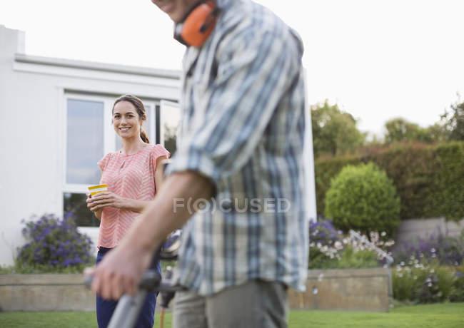 Woman watching male gardener at work in garden — Stock Photo