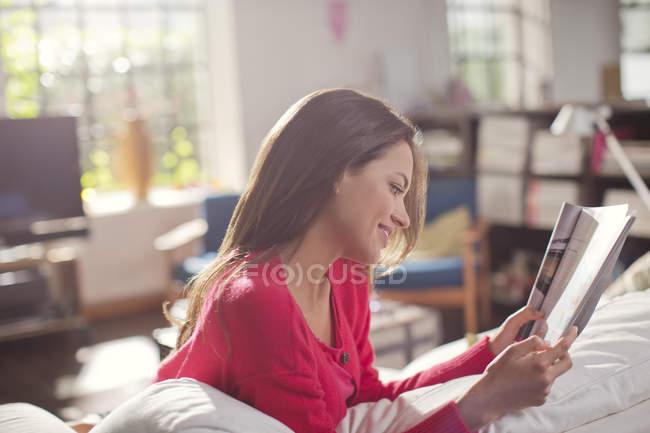 Zeitschrift Woman lesen auf sofa — Stockfoto