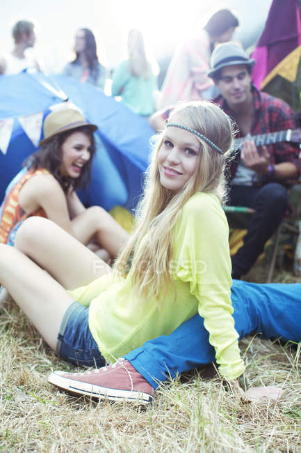 Portrait of woman hanging out with friends outside tents at music festival — Stock Photo