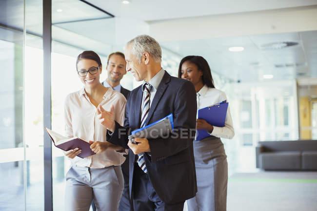 Les gens d'affaires marchent et parlent au bureau — Photo de stock