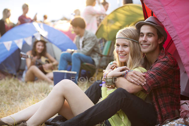 Couple hugging outside tent at music festival — Stock Photo