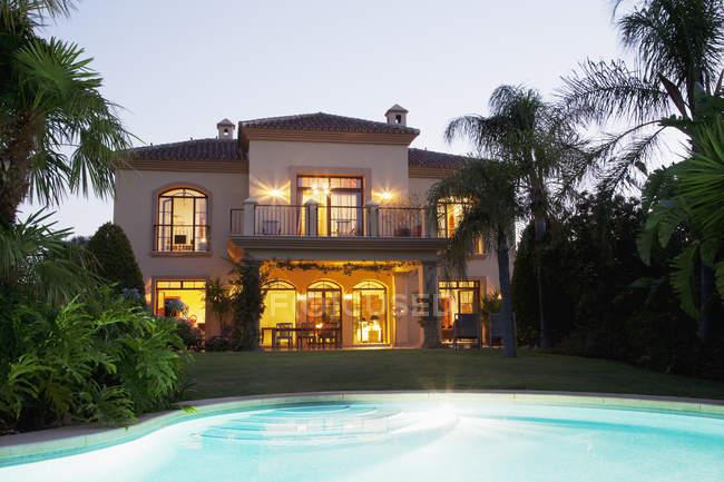 Luxury swimming pool and villa illuminated at night — Stock Photo
