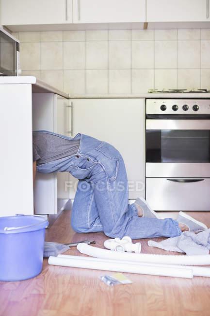 Skillful woman working under kitchen sink — Stock Photo