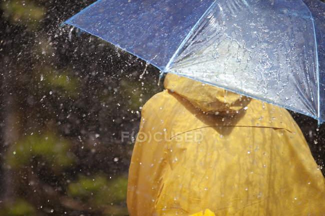 Vue arrière de la personne sous parapluie sous la pluie — Photo de stock