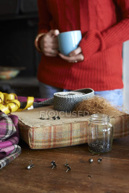 Woman having cup of coffee and crafting — Stock Photo
