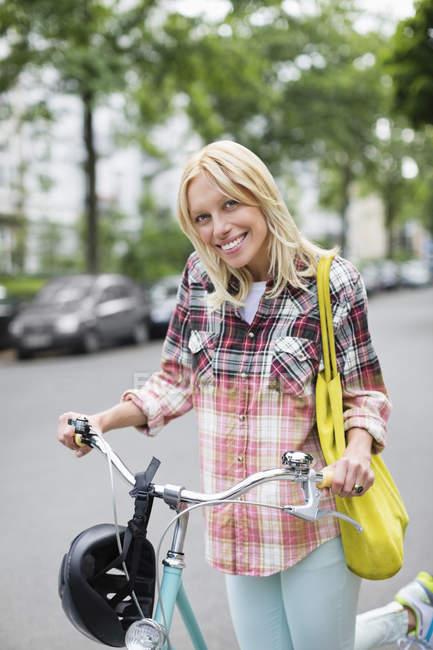 Woman pushing bicycle on city street — Stock Photo