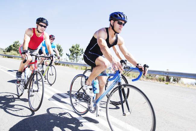 Велогонщики в гонке на сельской дороге — стоковое фото