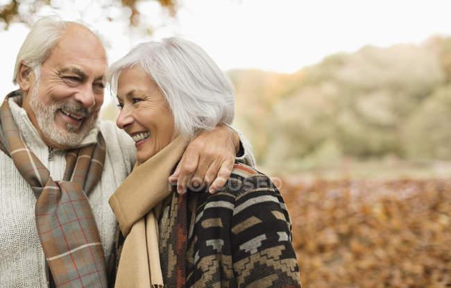 Старшая пара улыбается вместе в парке — стоковое фото
