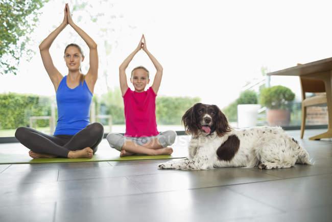 Hund sitzt mit Mutter und Tochter beim Yoga — Stockfoto