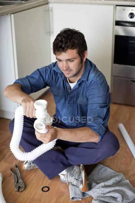 Водопроводчик работает на трубах под кухонной раковиной — стоковое фото