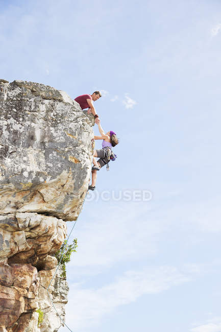Couple of climbers scaling steep rock face — Stock Photo