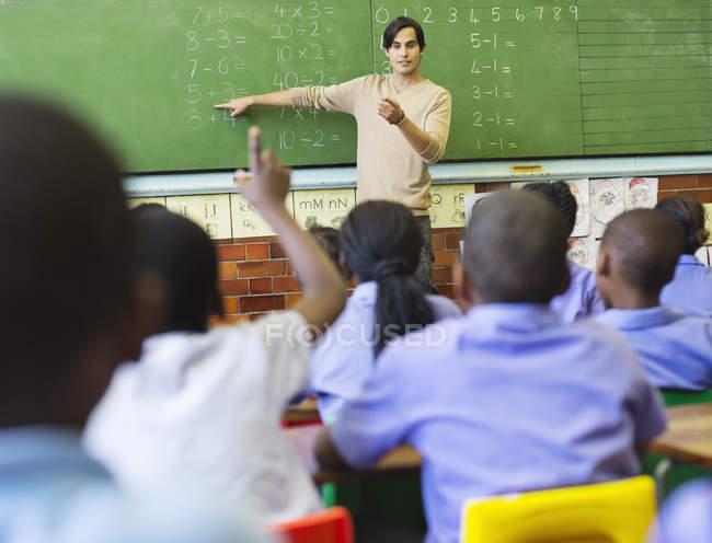 Lehrer im Gespräch mit afroamerikanischen Studenten an Tafel — Stockfoto