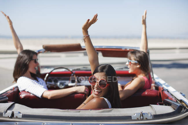 Women cheering in convertible car — Stock Photo
