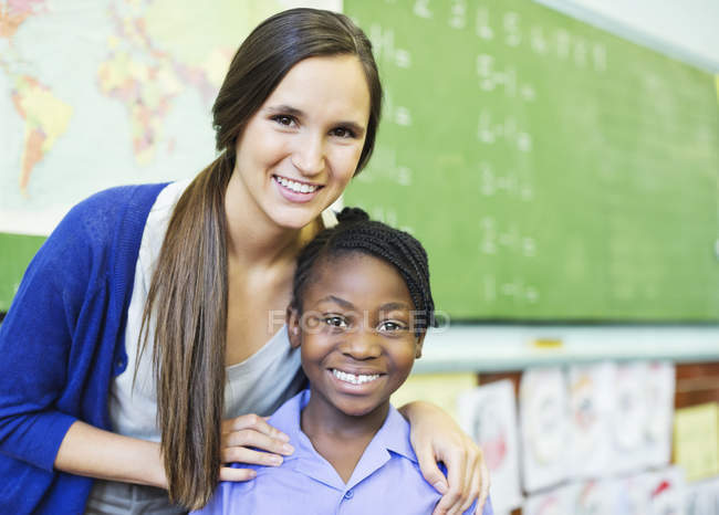 African american student and teacher smiling in class — Stock Photo