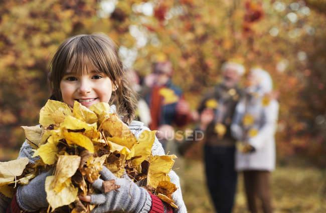 Chica jugando con hojas de otoño en el parque - foto de stock