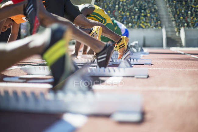 Runners poised at starting blocks on track — Stock Photo