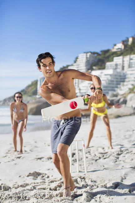 Щасливі Кавказький чоловік грає крикет на пляжі — стокове фото
