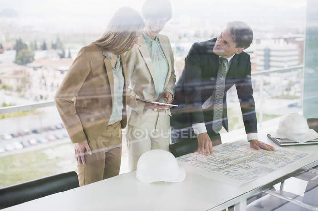 Architects with digital tablet reviewing blueprints in office — Stock Photo