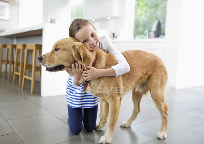 Sorridente ragazza abbracciare cane in cucina a casa moderna — Foto stock