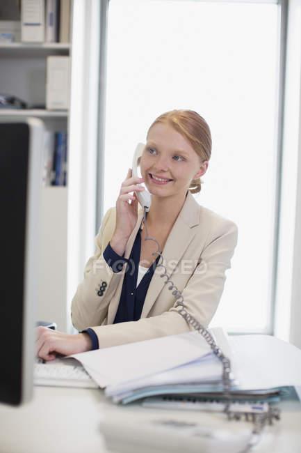 Smiling businesswoman talking on telephone — Stock Photo